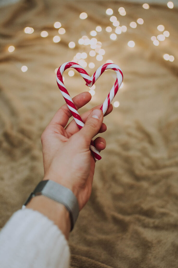 hand holding two candy canes in the shape of a heart on the beach with lights in the background